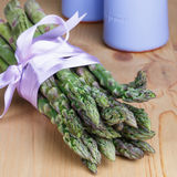 Groupe de lances vertes fraîches d'asperge attachées avec le ruban lilas Images libres de droits