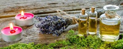 Groupe de lavande, de bougies et de bouteilles sèches d'huile parfumée Image stock