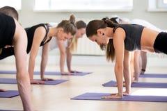 Groupe de leçon de pratique de yoga de jeunes sportifs, pose de planche photos stock
