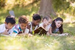 Groupe de livre de lecture d'amis tout en se trouvant sur le champ herbeux Photos stock