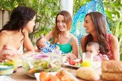 Groupe de mères avec des bébés appréciant le repas extérieur à la maison photos stock