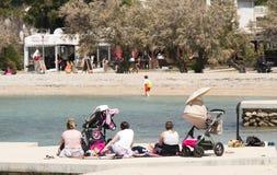 Groupe de mères avec des poussettes de bébé se reposant la morte-saison de plage au printemps photo libre de droits
