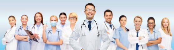 Groupe de médecins de sourire avec le presse-papiers au-dessus du gris photos stock