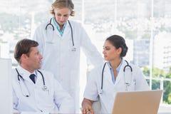 Groupe de médecins discutant et travaillant ensemble photographie stock