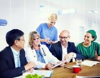 Groupe de médecins généralistes ayant une réunion Image libre de droits