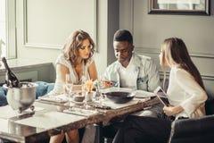 Groupe de métis de jeunes étudiants prenant le déjeuner ensemble en café Photo stock
