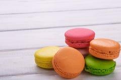 Groupe de macarons colorés sur le fond en bois blanc, avec la pièce pour l'espace de copie photographie stock