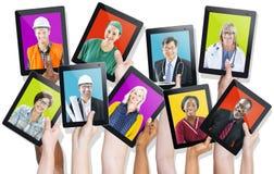 Groupe de mains tenant des Tablettes avec les visages des personnes Photo stock