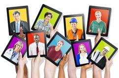 Groupe de mains tenant des Tablettes avec les visages des personnes Photo libre de droits