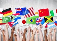 Groupe de mains tenant les drapeaux nationaux Photo libre de droits