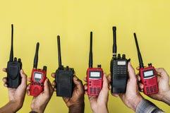 Groupe de mains tenant les radios bi-directionnelles portatives avec le fond jaune Images libres de droits