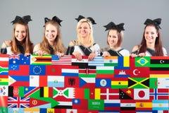 Groupe de majorettes tenant l'affiche avec des drapeaux Photo stock