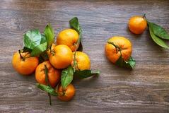 Groupe de mandarinas maduras frescas con las ramas en una tabla de madera Visión superior foto de archivo libre de regalías