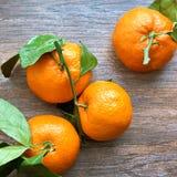 Groupe de mandarinas maduras frescas con las ramas en una tabla de madera Visión superior imagen de archivo