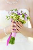 Groupe de mariage de fleurs dans des mains de jeune mariée Image stock