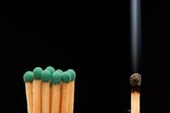 Groupe de matchs en bois verts se tenant avec le match fumé brûlé Image stock
