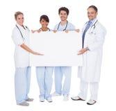 Groupe de médecins présent le panneau vide Image stock