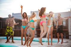 Groupe de meilleurs amis ayant l'amusement à la piscine Images libres de droits