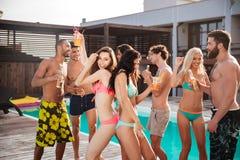 Groupe de meilleurs amis ayant la danse d'amusement à la piscine Photographie stock libre de droits