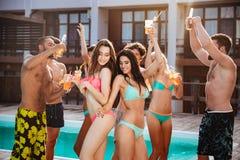 Groupe de meilleurs amis ayant la danse d'amusement à la piscine Image libre de droits