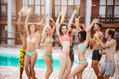 Groupe de meilleurs amis ayant la danse d'amusement à la piscine Images libres de droits