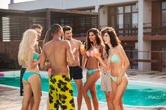 Groupe de meilleurs amis ayant la partie par la piscine dehors Image libre de droits