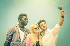 Groupe de meilleurs amis heureux multiraciaux prenant un selfie de vintage Photographie stock libre de droits