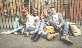 Groupe de meilleurs amis multiraciaux heureux ayant l'amusement utilisant le téléphone portable Images libres de droits