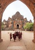 Groupe de moines de novice entrant dans heureusement le temple de Dhammayangyi pour des prières du matin, Bagan, Myanmar photographie stock libre de droits