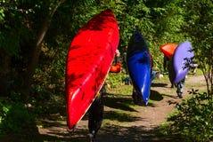 Groupe de paddlers portant leurs canoës de whitewater photographie stock libre de droits