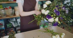 Groupe de participation de fleuriste de jeune dame de belles fleurs s'chargeant du bouquet dans le magasin banque de vidéos