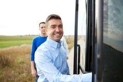 Groupe de passagers masculins heureux montant à bord de l'autobus de voyage Images stock