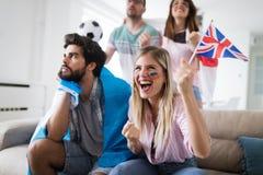 Groupe de passionés du football déçus et heureux observant une partie de football sur le divan Photo stock