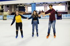 Groupe de patinage de glace adolescent d'amis sur la patinoire ensemble Image libre de droits