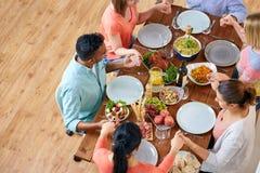 Groupe de personnes à la table priant avant repas Image stock