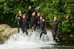 Groupe de personnes adultes sautant dans la petite cascade Photo libre de droits