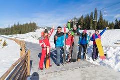 Groupe de personnes amis de sourire heureux gais de montagne de neige de Ski And Snowboard Resort Winter en vacances Image stock