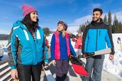 Groupe de personnes amis de sourire heureux gais de montagne de neige de Ski And Snowboard Resort Winter parlant des vacances Photographie stock libre de droits