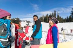 Groupe de personnes amis de sourire heureux gais de montagne de neige de Ski And Snowboard Resort Winter parlant des vacances Photos stock