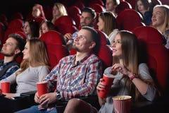 Groupe de personnes appréciant le film au cinéma Images stock
