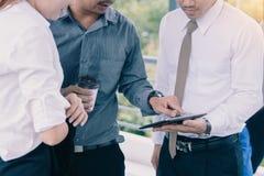 Groupe de personnes asiatiques d'affaires tenant et parlant du compte rendu succinct sur l'écran de comprimé avec la prise temps  photographie stock