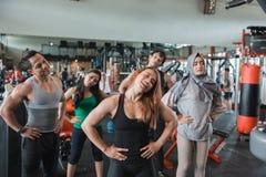 Groupe de personnes au centre de fitness s'étendant pour réchauffer photos stock