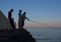 Groupe de personnes au coucher du soleil pour pêcher les poissons d'amorce du dock Photographie stock libre de droits