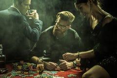 Groupe de personnes avec des boissons jouant le tisonnier dans le casino Image stock