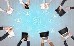 Groupe de personnes avec des dispositifs dans des mains travaillant aux ordinateurs portables et aux comprimés avec le concept de photo stock