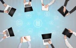 Groupe de personnes avec des dispositifs dans des mains travaillant aux ordinateurs portables et aux comprimés avec le concept de image stock