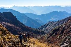 Groupe de personnes avec des sacs à dos marchant sur la traînée sur le voyage de l'Himalaya Photos stock