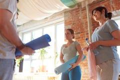 Groupe de personnes avec des tapis au studio ou au gymnase de yoga Image stock