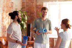 Groupe de personnes avec des tapis au studio ou au gymnase de yoga Photo libre de droits