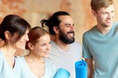 Groupe de personnes avec des tapis au studio ou au gymnase de yoga Photographie stock